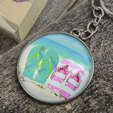 Beach themed flip flop design key chain with a clear glass dome and all metal construction